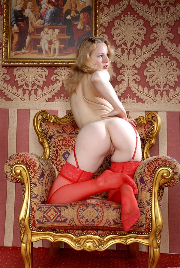 Молодая блондинка в одних чулках сидит в позолоченном кресле секс фото и порно фото